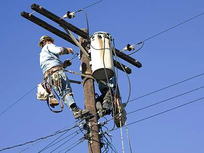A lineman makes repairs to power lines following a storm.