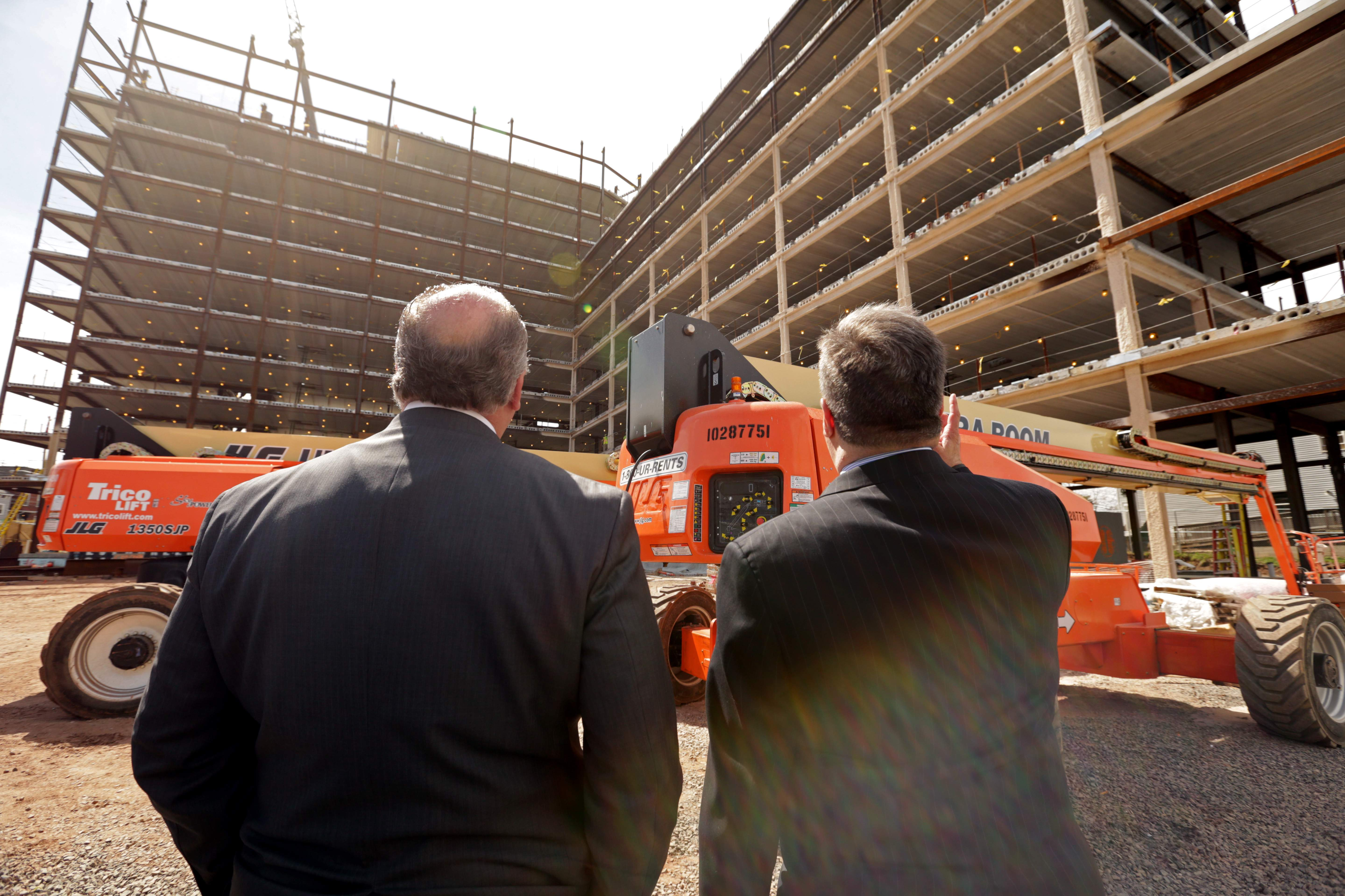 Chris Paladino, right, takes Senate President Steve Sweeney on a tour of DEVCO's projects in New Brunswick.  The two are pictured looking at the University Apartments project.