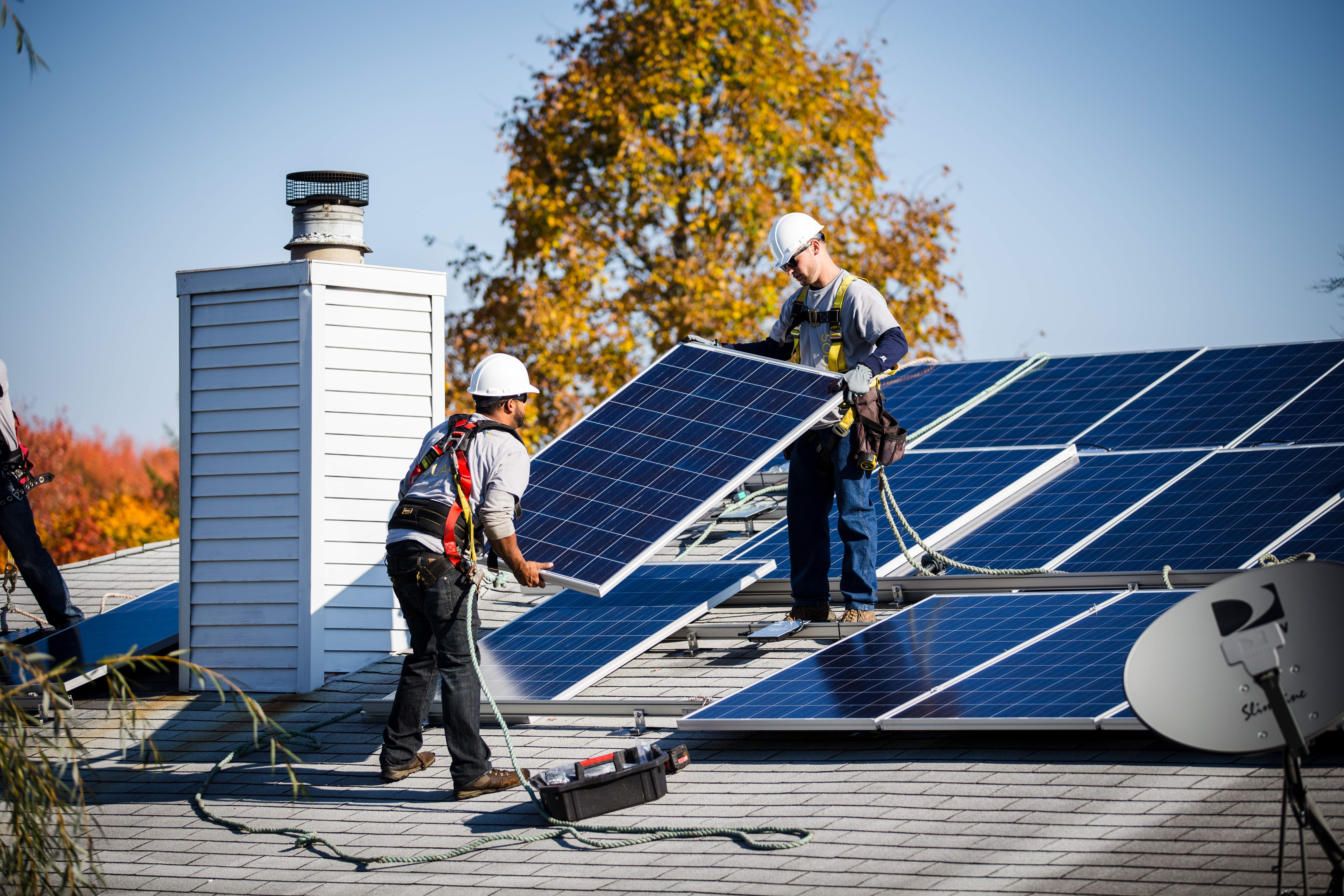 Installers work on an NRG residential solar project in Marlboro.