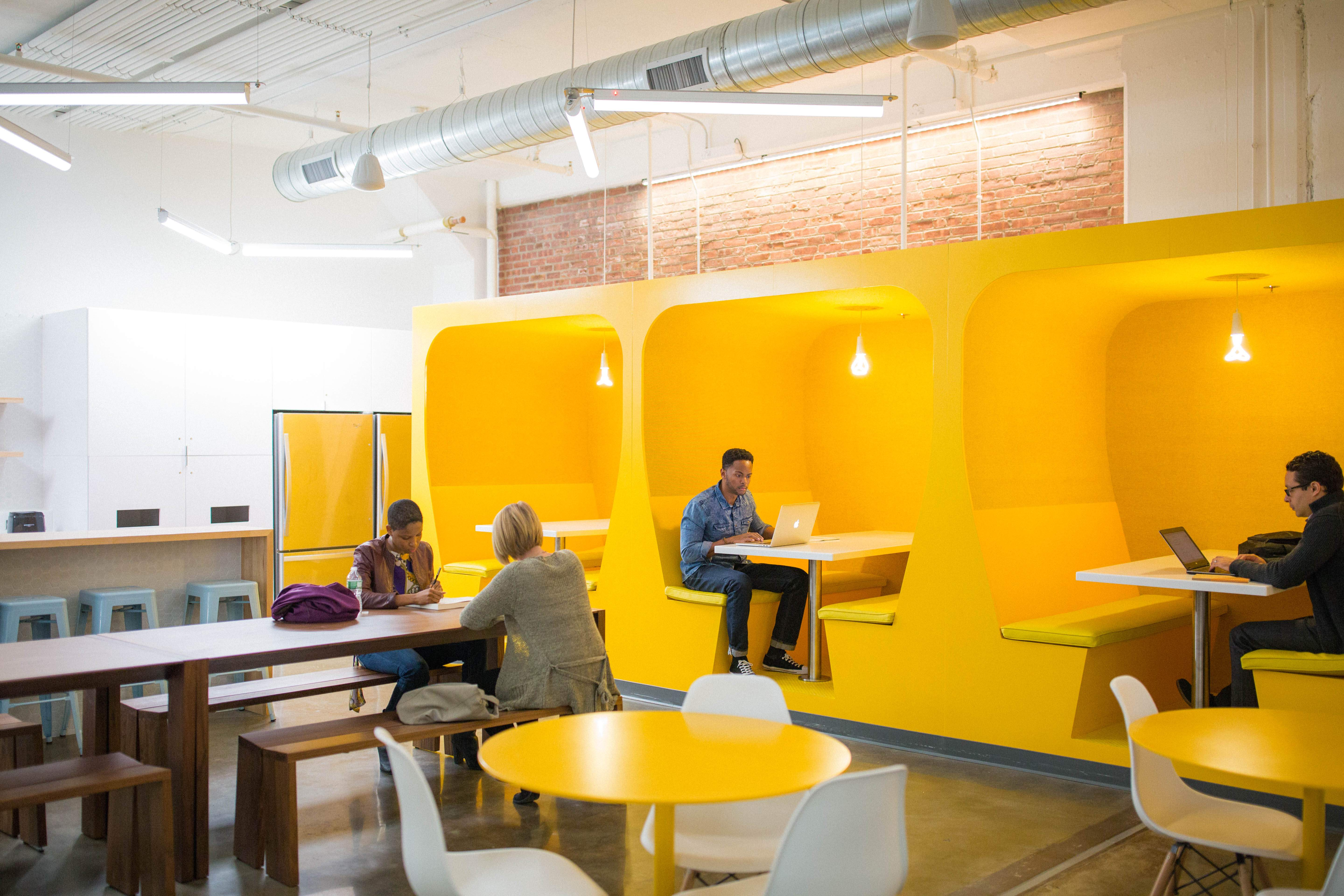 Professionals utilize sleek coworking spaces that have been planned for the facility.