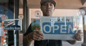 A small business owner hangs an open sign in a door window.