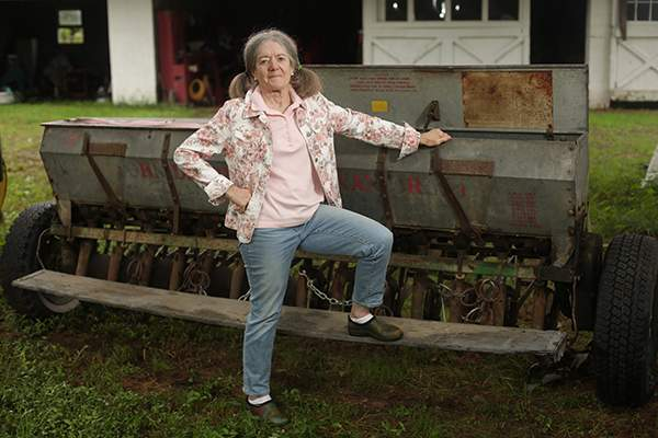 Mary Beth Jennings, co‑owner of The Jennings Farm in Medford, with the old seed drill she plans to use to plant hemp seeds if and when it becomes legal.