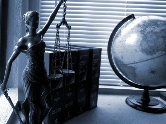 Attorney, lawyer or law professional's desk with law books, scales of justice and a globe.