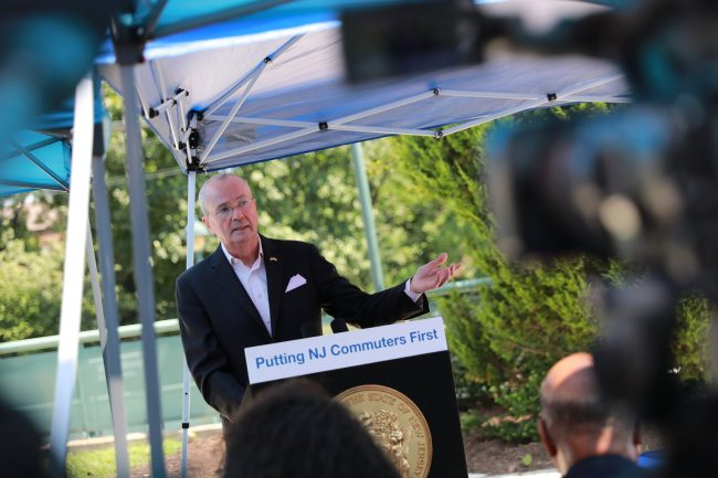 Gov. Phil Murphy signs an executive order requiring New Jersey Transit to release monthly rail performance metrics at the Bay Street Train Station in Montclair on Aug. 19, 2019.