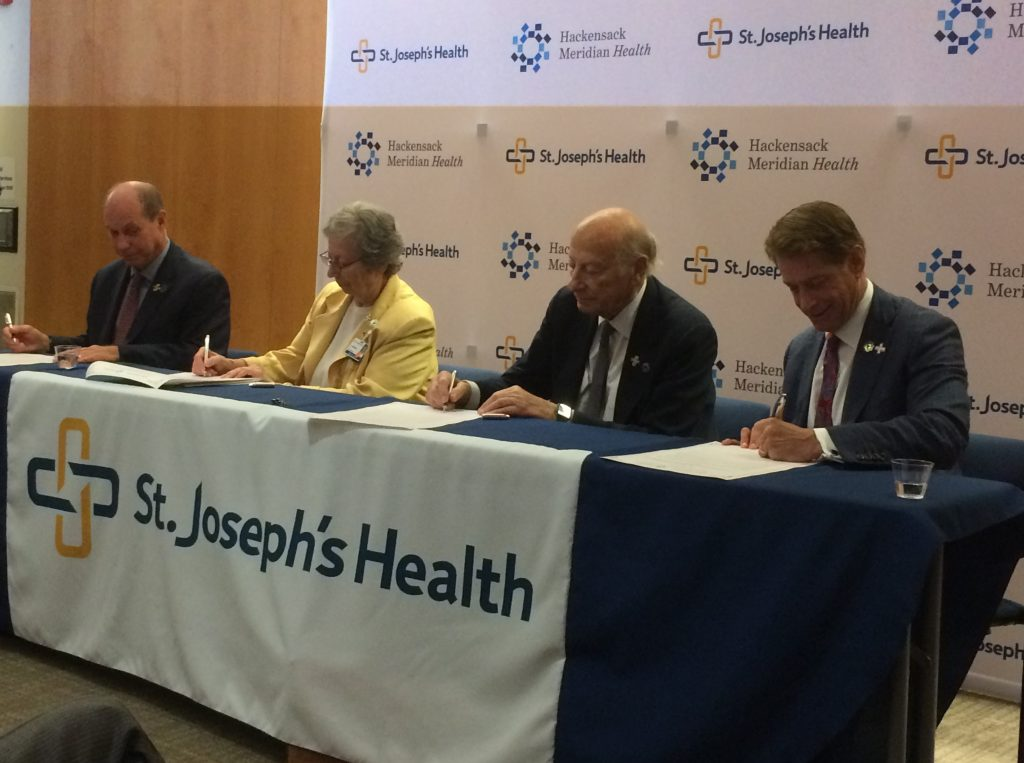 From left, St. Joseph's Health President and CEO Kevin Slavin, St. Joseph's Health Chair of the Board of Trustees at Sister Marilyn Thie, HMH Chair of the Board of Trustees Gordon Litwin and HMH President and CEO Robert Garrett sign an agreement establishing a strategic partnership between the health systems on Sept. 25, 2019 at St. Joseph's University Medical Center.