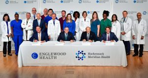 Englewood Health and Hackensack Meridian Health announced Oct. 15 they signed a definitive agreement to merge. Seated from left, Warren Geller, president and CEO, Englewood Health; Thomas Senter, chairman, board of trustees, Englewood Health; Gordon Litwin, chairman, board of trustees, Hackensack Meridian Health; and Robert C. Garrett, CEO, Hackensack Meridian Health are joined by physicians, nurses and other clinical staff from Englewood Health and Hackensack Meridian Health.