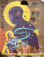 """At 10-stories high, Magnitude and Bond at 97 Halsey St. from A Womb of Violet Collective, led by fayemi shakur, Layqa Nuna Yawar and Kelley Prevard, is the tallest mural in the city, to date. The piece pays tribute to Gladys Barker Grauer – Newark's """"Mother of the Arts"""" – and to poet Breya 'Blkbrry Molassez' Knight."""