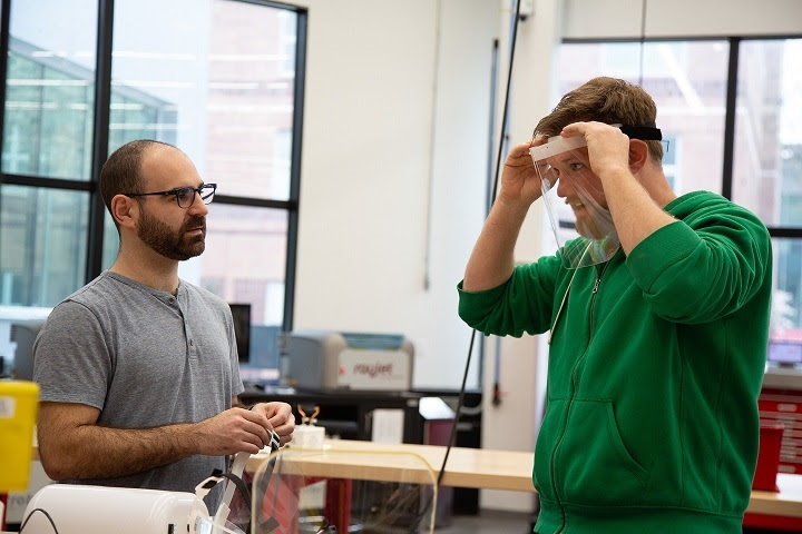 Justin Suriano and Daniel Brateris try on a face shield they designed and fabricated in the Makerspace at NJIT. - NJIT
