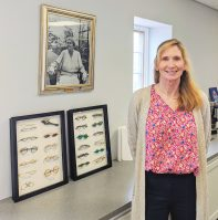 Jean Gajano, executive director of New Eyes, standing in front of photo of founder Julia Lawrence Terry. - NEW EYES