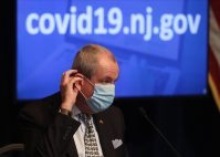 Gov. Phil Murphy puts on his mask at the conclusion of his daily COVID-19 press briefing at the the War Memorial in Trenton on April 24, 2020.