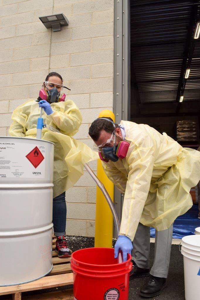 Jennifer Burns, pharmacy coordinator, Inspira Medical Center Vineland, and Ed Dix, director of Pharmacy, Inspira Medical Center Mullica Hill, transfer isopropyl alcohol to a bucket in preparation for mixing a batch of hand sanitizer.