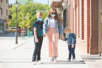 Young mother and kids on a walk during coronavirus epidemic. Family wearing medical masks. People in safety face mask to protect coronavirus. Children and mom at city street. Lifestyle 2020.