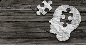 Mental health symbol Puzzle and head brain concept as a human face profile made from crumpled white paper with a jigsaw piece cut out on a rustic old double page spread horizontal wood background.