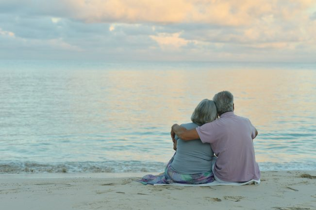 An older couple sits together on the beach.