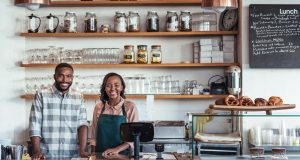 Portrait of two smiling young African American entrepreneurs standing together behind the counter of their coffee shop