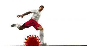Football or soccer player kicking, punching model of coronavirus - fighting with epidemic concept. Professional sportsman. Epidemic spreading, protection, everyday's struggle for life and health.