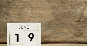 White block calendar present date 19 and month June on wood background
