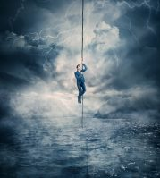 Businessman salvation, surviving the storm buiness concept as a scared man hanging on a chain above the ocean water, trying to climb up. Risk symbol, metaphor for conquering adversity and overcoming challenges.