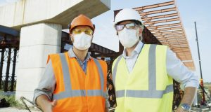 Mature and adult men in helmet and protective masks talking with each other while working on construction site during pandemic