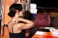 A woman models a luxury ring, earrings, and hand bag from ShopWorn's Cresskill warehouse.- SHOPWORN