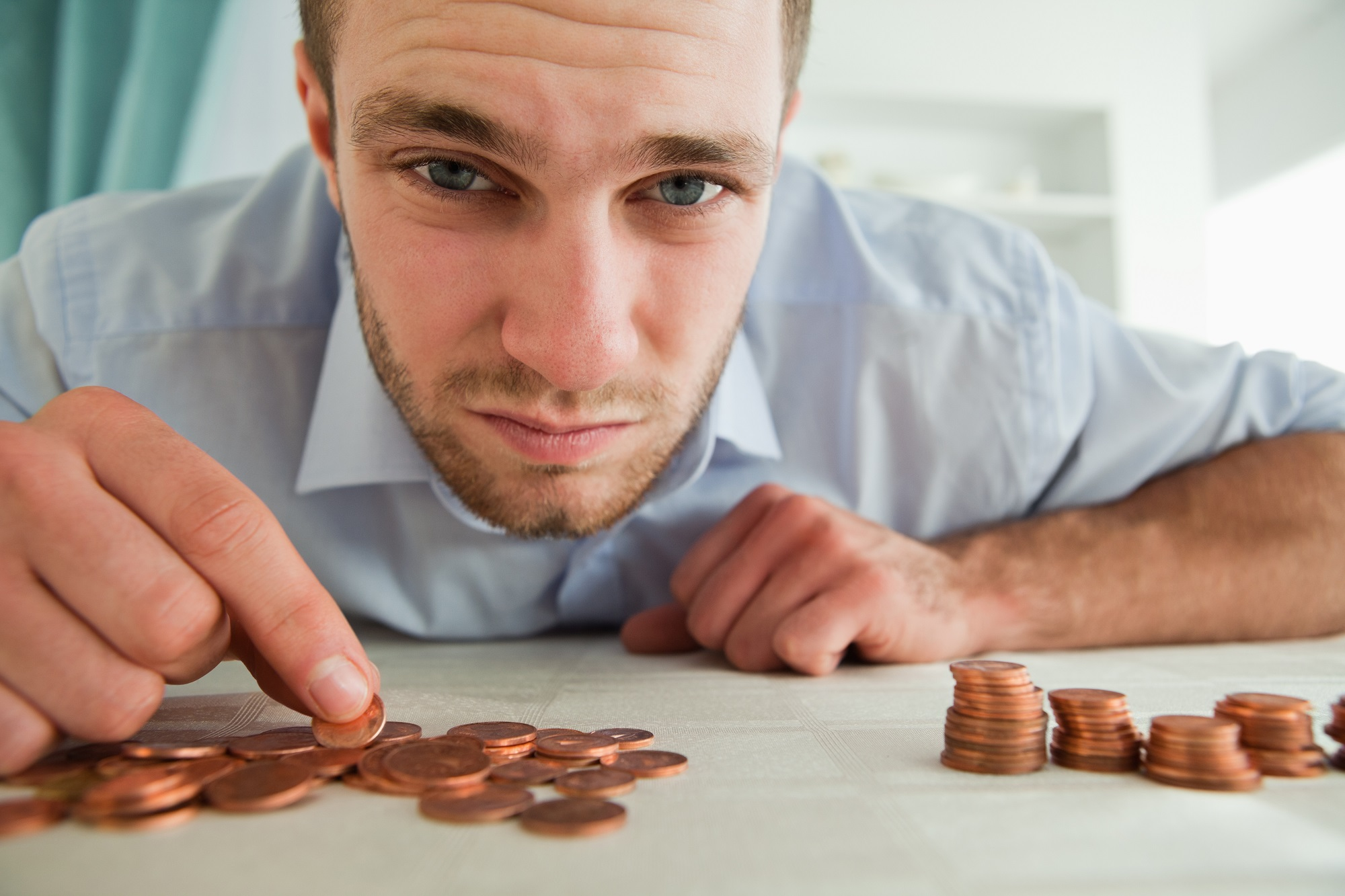 Desperate young businessman counting his change