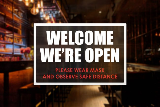 Welcome sign of a bar or pub, with reminder to wear mask and observe social distancing. Concept of new normal operations in a bar or restaurant.