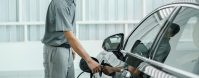 Senior Technician is charging the electric car or EV in service center for maintainance, Eco-friendly alternative energy concept