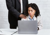 Workplace harassment concept. Young female secretary looking at boss's hand on her shoulder with disgust. Businessman using his job position to molest female employee at company office