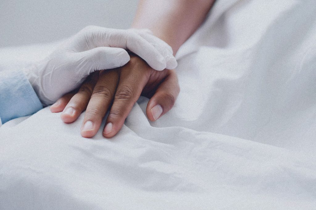 Doctors wear medical gloves holding touching hands man patient with love, care, helping, encourage and empathy at nursing hospital ward.healthy strong medical concept