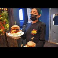 A server at Steve's Burgers in North Bergen where's a mask while delivering food to a table. - STEVE'S BURGERS