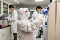 Researchers in protective gear work in a laboratory.